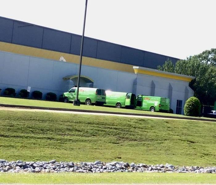 Green SERVPRO vehicles parked outside a commercial facility.