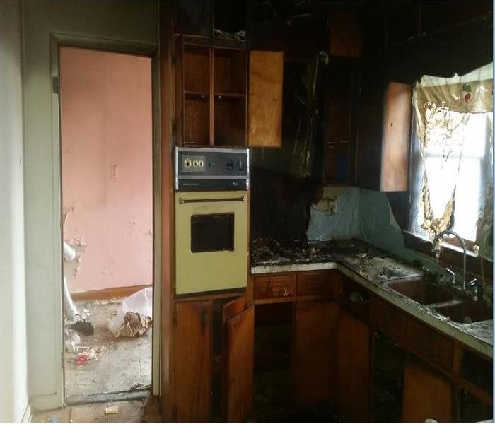 A kitchen burned by fire with soot covering the walls and counters.