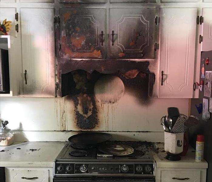 Fire damage on cabinets from a fire on the stove.