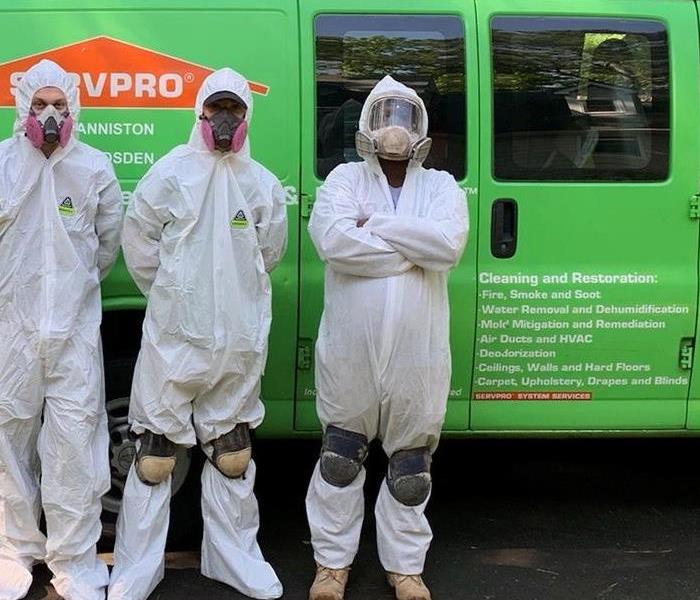 Three crew members in tyvek suits next to our green van.