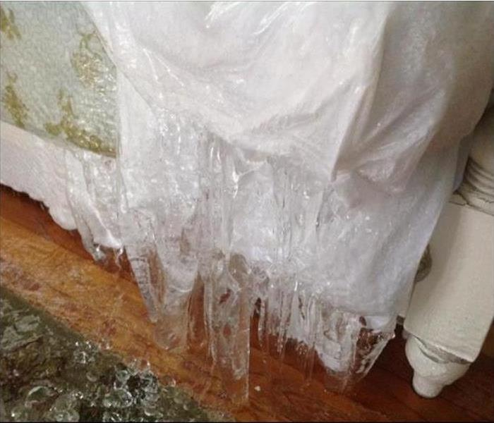 Frozen water under a window in a home.
