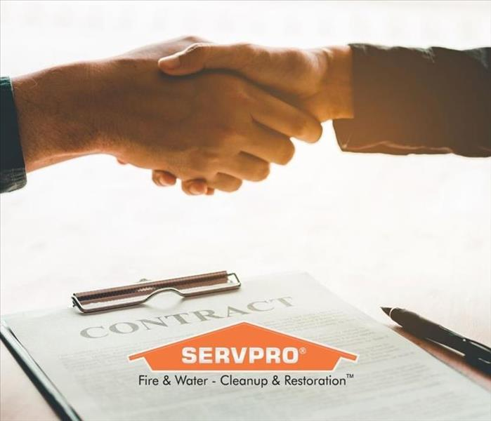 Two people shaking hands over a contract with a SERVPRO logo.