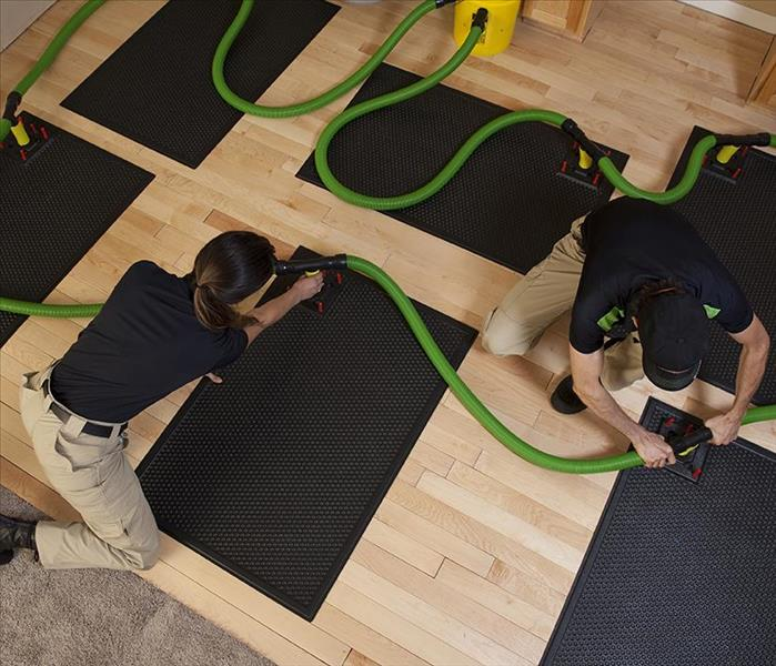 SERVPRO technicians placing a mat drying system on a floor.