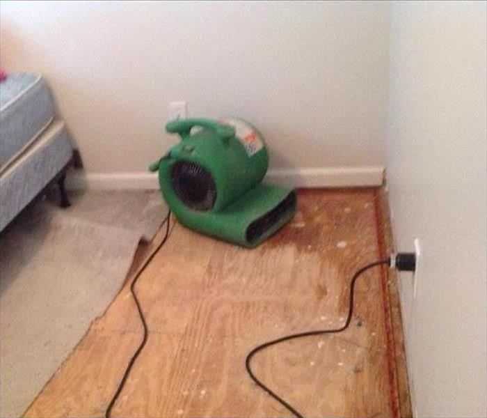 A green SERVPRO air mover set on plywood to dry the wet flooring after a water damage.