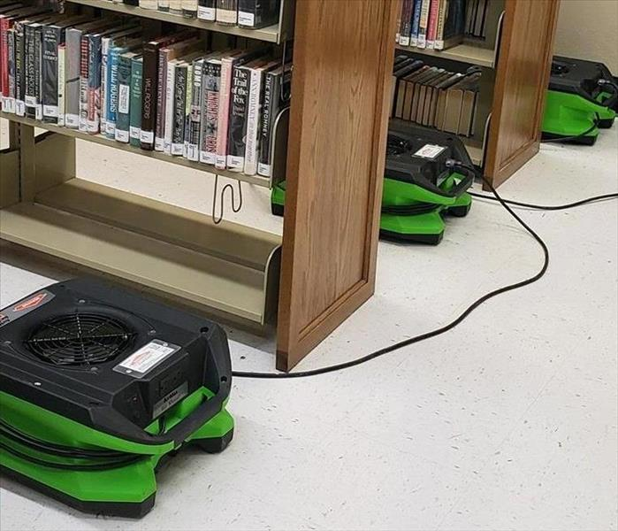 SERVPRO fans set between the aisles of books in the library.