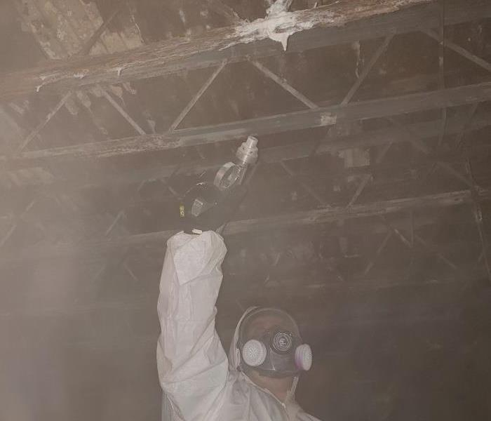 A SERVPRO employee soda blasting mold in a crawlspace.
